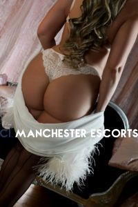 Tessa rear view stood in front of a pink back drop wearing white lace panties and holding a white shawl