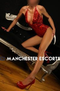Naomi kneeling on a black couch wearing a red sparkly body stocking.