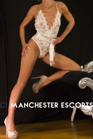 Naomi kneeling on a guilded couch wearing a white lace body stocking.