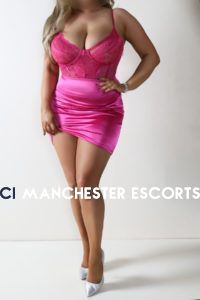 Felicity stood posing in a hot pink satin and lace dress and silver stiletto shoes