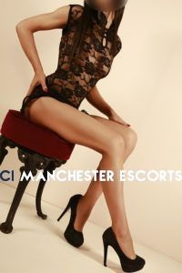 Alisha sat on a red stool legs pointed looking sexy in black see through lace dress