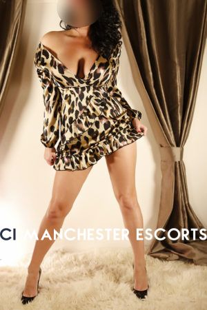 Tia is a leopard print dress stood up showing her long legs