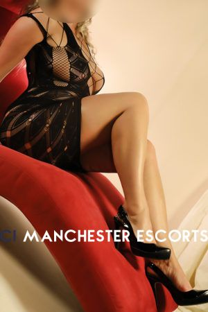Sally Lay across chaise lounge wearing a black revealing dress and black high heels