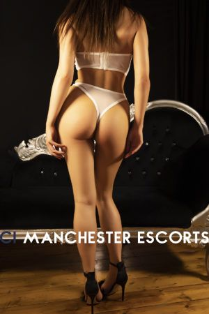 Amelia stood in front of a black chais long showing her perk bottom in a white thong and bra
