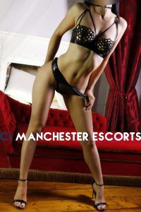 Kayleigh stood in front of a chais long hip popped to the side wearing black patent set and black heels