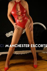 Claudia is standing in front of a black sofa chair wearing a red leather body suit with red high heels to match