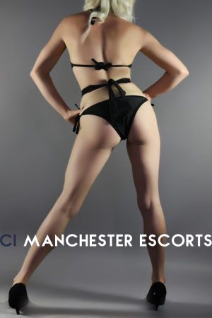 Polly rear view hands on hips and legs apart wearing a black bodysuit and black heels