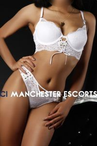 Close up of Carmel on a black background wearing a cheeky white 2 piece lingerie set and red heels