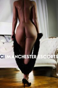 Mya fully naked stood in front of a white sofa legs crossed holding a black fur scarf
