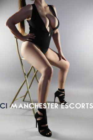 Cassie sat on a stool legs open wearing a revealing bodysuit