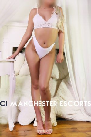 Lorna stood up wearing cream lingerie bare legged with high heels