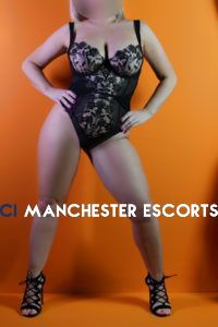 Marilyn stood in front of an orange wall legs apart wearing a gorgeous black bodysuit and high heels
